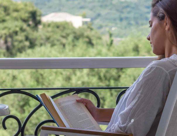 Frau liest Buch auf dem Panorama Balkon